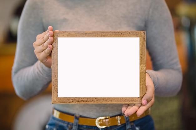 Donna che tiene struttura di legno in bianco in caffetteria