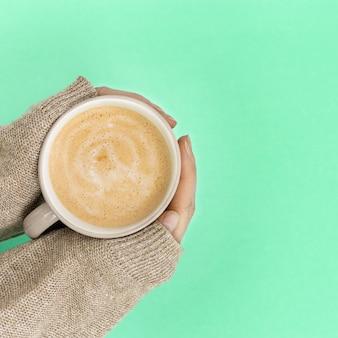 Donna che tiene tazza di caffè sul fondo della menta di colore di tendenza. chiudere le mani in maglione caldo con cappuccino caldo. vista dall'alto e copia spazio.