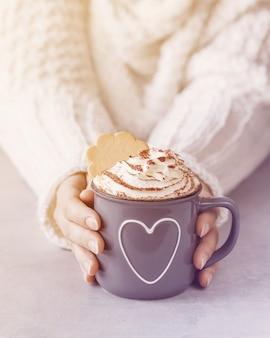 Donna che tiene tazza di metallo grigio di cioccolata calda con panna montata nelle mani