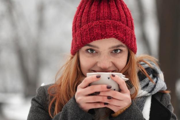Donna che tiene tazza di tè vicino al suo viso