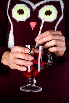 Donna che tiene tazza di vetro di vin brulé delizioso natale in mani, primo piano