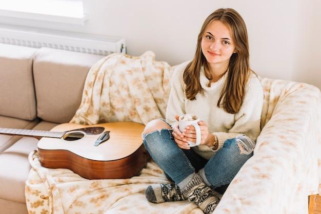 Donna che tiene tazza vicino alla chitarra sul divano