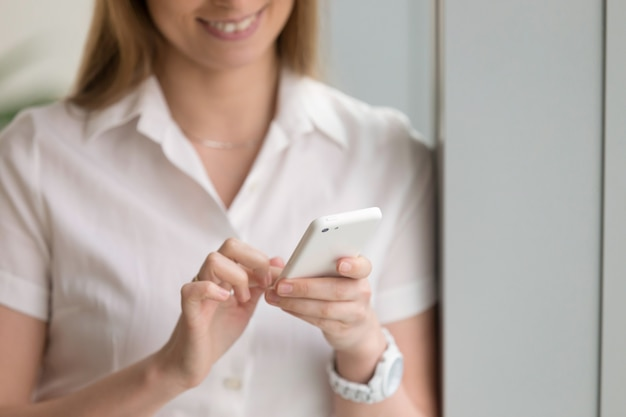 Donna che tiene telefono bianco, mani femminili facendo uso dello smartphone, fine su