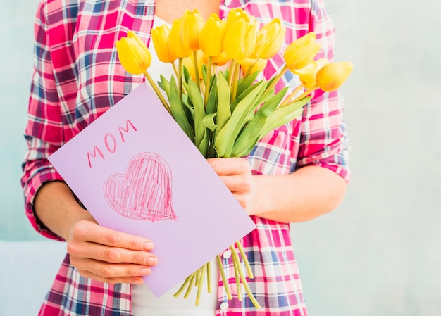 Donna che tiene tulipani e biglietto di auguri