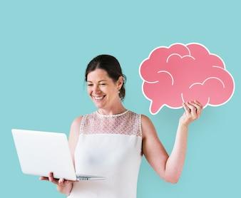 Donna che tiene un'icona del cervello e utilizzando un computer portatile