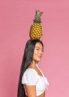 Donna che tiene un ananas sulla sua testa lateralmente