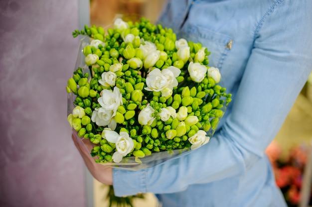 Donna che tiene un bellissimo bouquet di fiori nei toni del bianco e verde