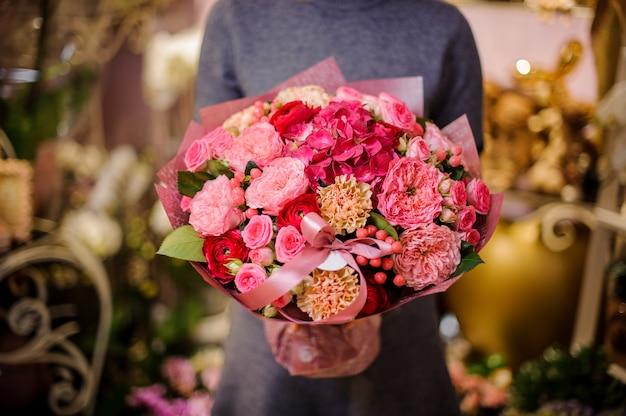 Donna che tiene un bellissimo bouquet nei toni del rosa