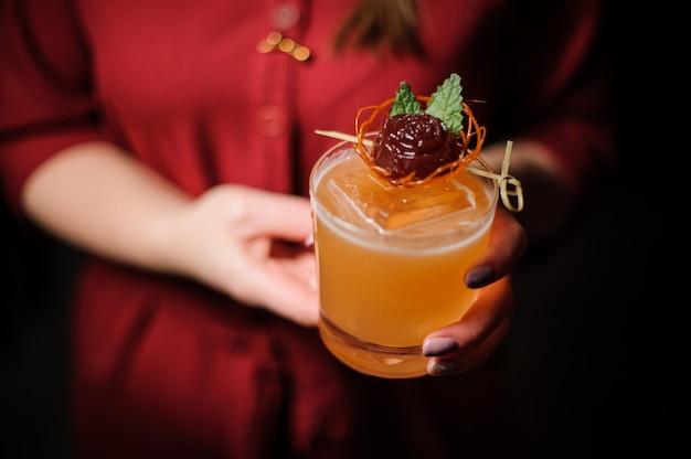 Donna che tiene un bicchiere con un cocktail decorato
