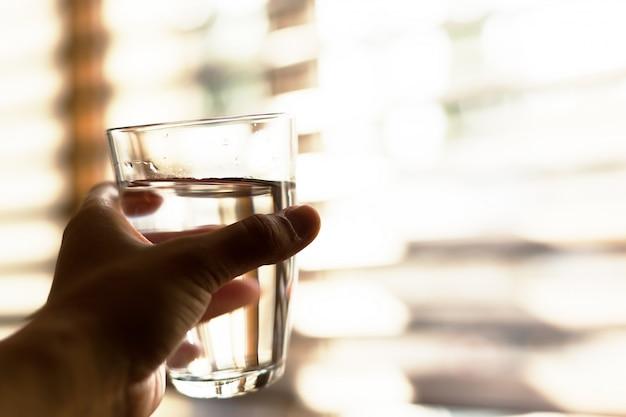 Donna che tiene un bicchiere d'acqua, primo piano