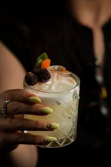 Donna che tiene un bicchiere di cocktail guarnito con lamponi secchi