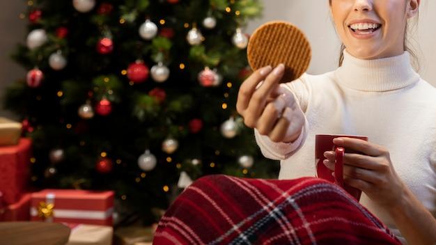 Donna che tiene un biscotto e una tazza rossa