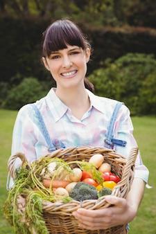 Donna che tiene un cestino delle verdure appena raccolte in giardino