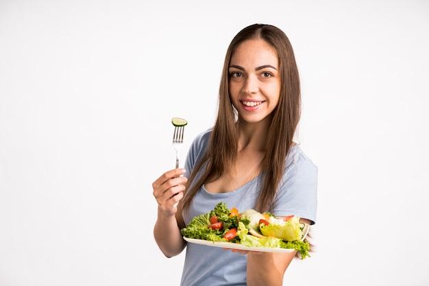 Donna che tiene un cetriolo e un'insalata