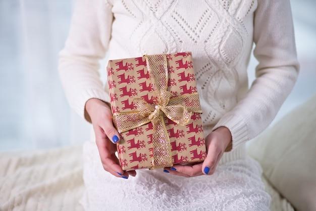 Donna che tiene un contenitore di regalo di natale in mani sul bianco