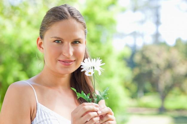 Donna che tiene un fiore nel parco