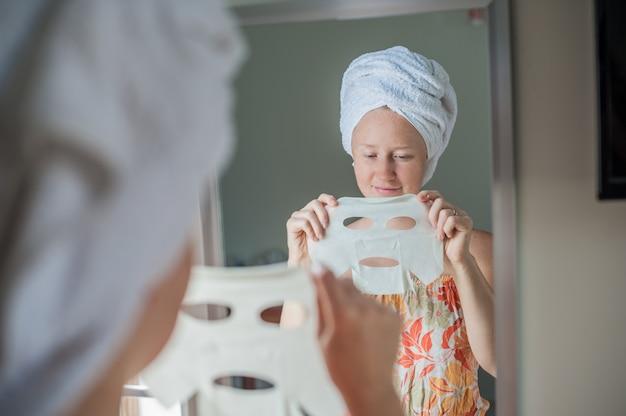 Donna che tiene un foglio maschera facciale