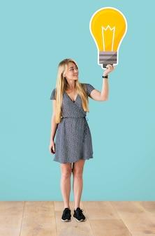 Donna che tiene un'icona di lampadina