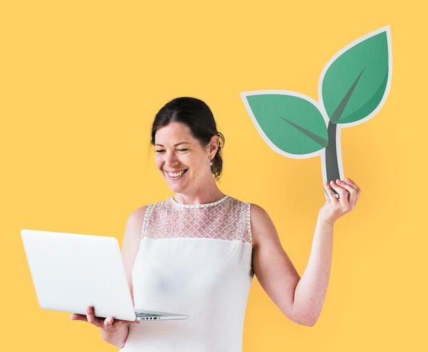 Donna che tiene un'icona di pianta e utilizzando un computer portatile