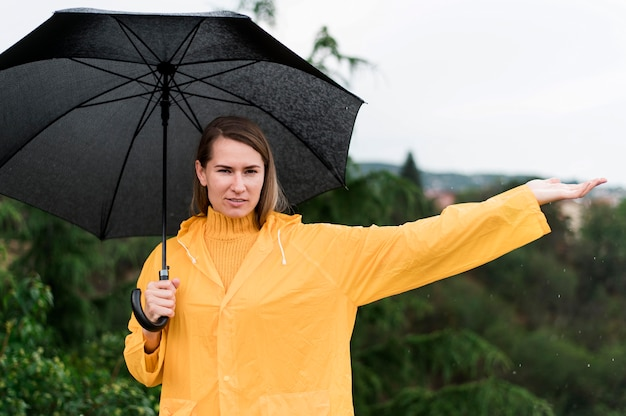 Donna che tiene un ombrello nero aperto