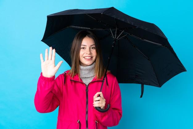 Donna che tiene un ombrello sopra la parete blu isolata