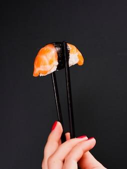 Donna che tiene un paio di bacchette con sushi di salmone