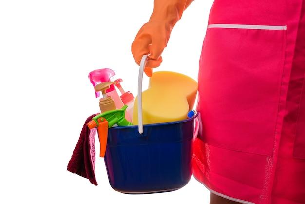 Donna che tiene un secchio pieno di prodotti per la pulizia isolato su sfondo bianco