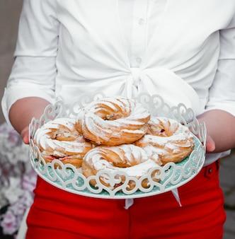 Donna che tiene un vassoio con pasticceria francese con fragole e panna