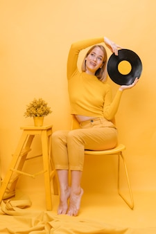 Donna che tiene un vinile in una scena gialla