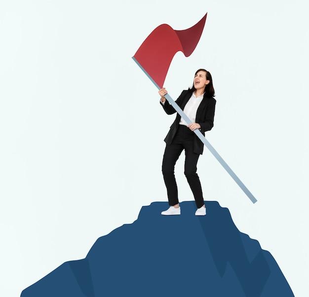 Donna che tiene una bandiera sulla cima di una montagna