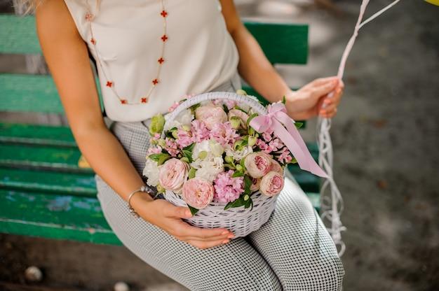 Donna che tiene una bella composizione di fiori nel cestino di vimini