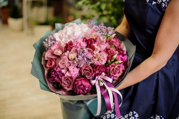 Donna che tiene una bella e morbida composizione di fiori