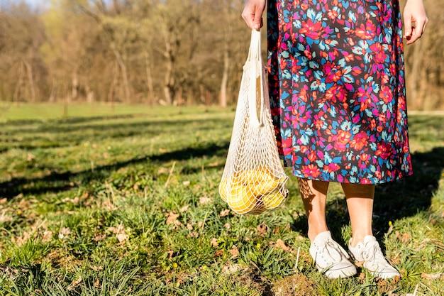 Donna che tiene una borsa di frutta nel parco