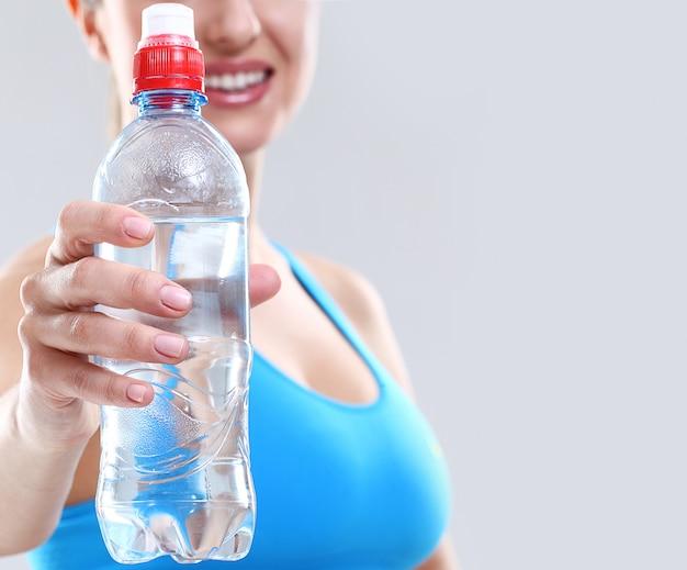 Donna che tiene una bottiglia di acqua