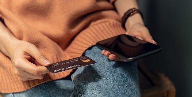 Donna che tiene una carta di credito e uno smartphone