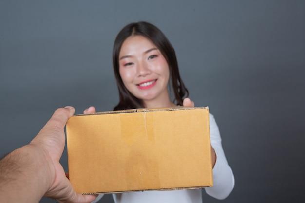 Donna che tiene una casella di posta marrone fatto gesti con la lingua dei segni.