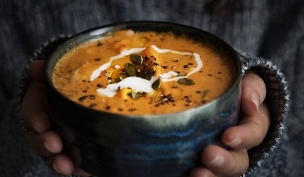 Donna che tiene una ciotola di idea di ricetta di fotografia di cibo zuppa