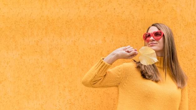 Donna che tiene una foglia di autunno con lo spazio della copia