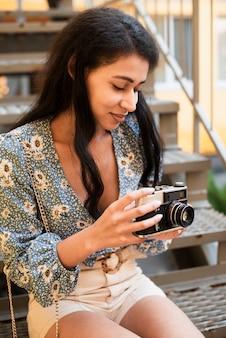 Donna che tiene una macchina fotografica d'annata e che esamina le foto