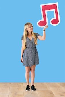 Donna che tiene una nota musicale in uno studio