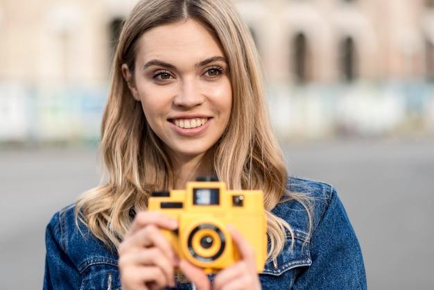 Donna che tiene una retro macchina fotografica gialla all'aperto
