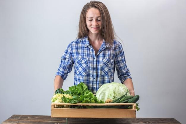 Donna che tiene una scatola di verdure fresche sane