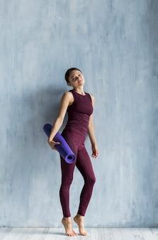 Donna che tiene una stuoia di yoga in sua mano