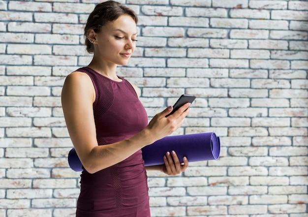 Donna che tiene una stuoia di yoga mentre levandosi in piedi sul suo telefono