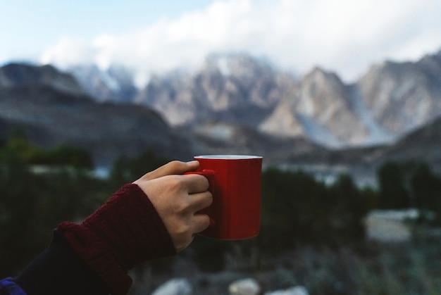 Donna che tiene una tazza che domina le montagne dell'himalaya