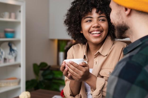Donna che tiene una tazza di caffè e che esamina il suo ragazzo