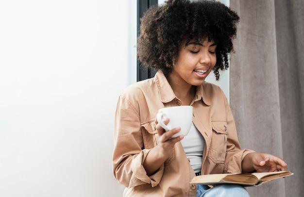Donna che tiene una tazza di caffè e una lettura