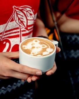 Donna che tiene una tazza di cappuccino con latte art a forma di orso