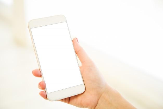 Donna che tiene uno smartphone in bianco dell'oro rosa