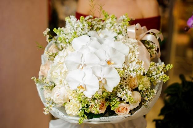 Donna che tiene uno splendido mazzo di fiori